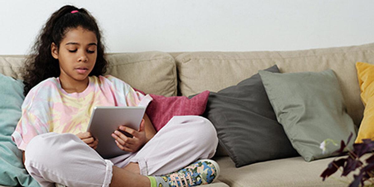 A girl sits on a sofa cross-legged using an iPad