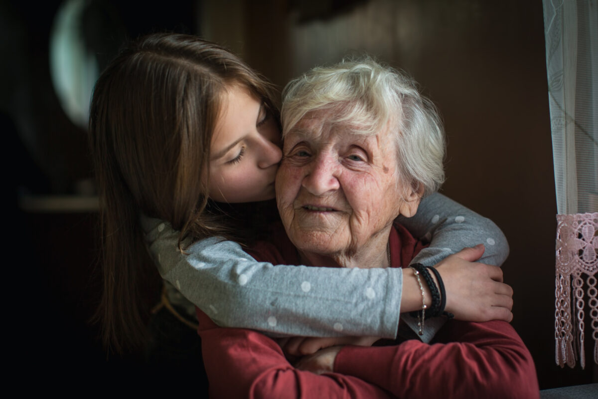 A seated elderly woman being hugged by her granddaughter.