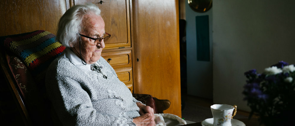 Eldre mann sitter i en stol