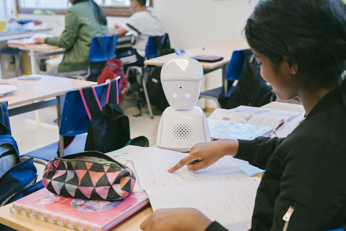 AV1 on a desk in a classroom. A girl points to a page in a book, which the AV1 looks down at