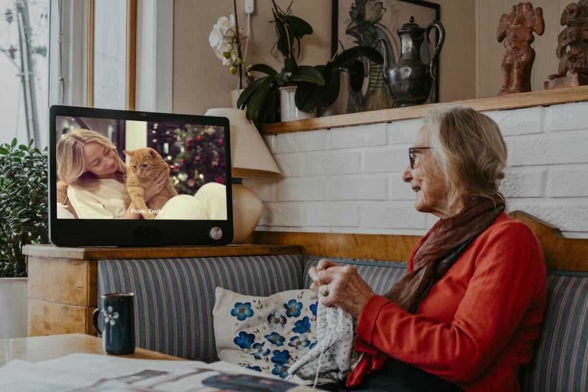 Eldre dame strikker og ser på Komp